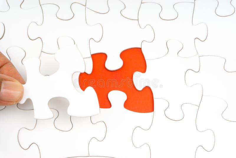 La main a mis le dernier morceau de plan rapproché de puzzle denteux pour accomplir la mission illustration stock