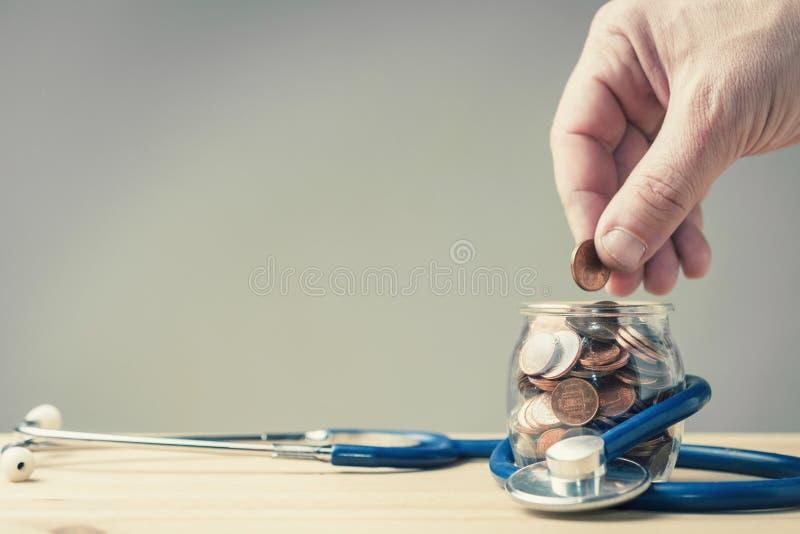La main a mis la pièce de monnaie dans un pot enveloppé dans un stéthoscope photographie stock libre de droits