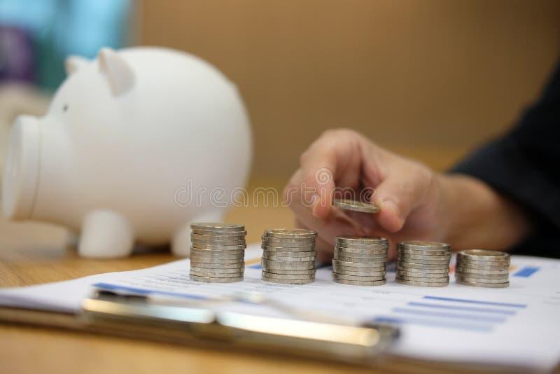la main a mis la pièce de monnaie sur la pile l'épargne d'argent, concept de paiement en espèces photographie stock libre de droits