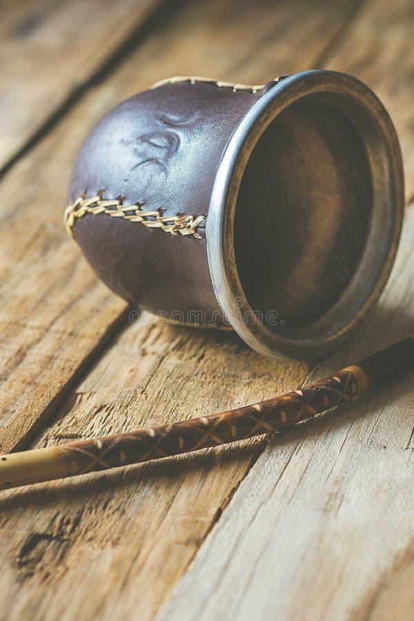 La main a ouvré Yerba artisanal Mate Tea Leather Calabash Gourd avec la paille sur le fond superficiel par les agents en bois de  images stock
