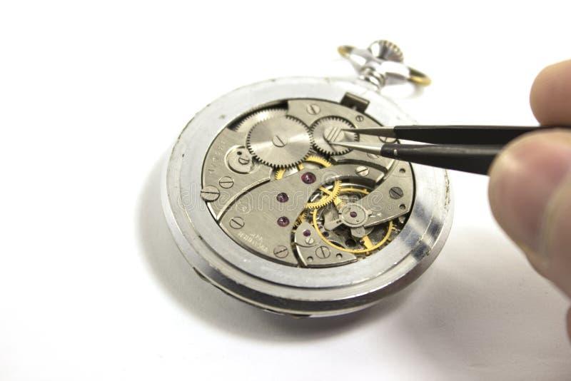 La main répare une vieille montre mécanique D'isolement image stock