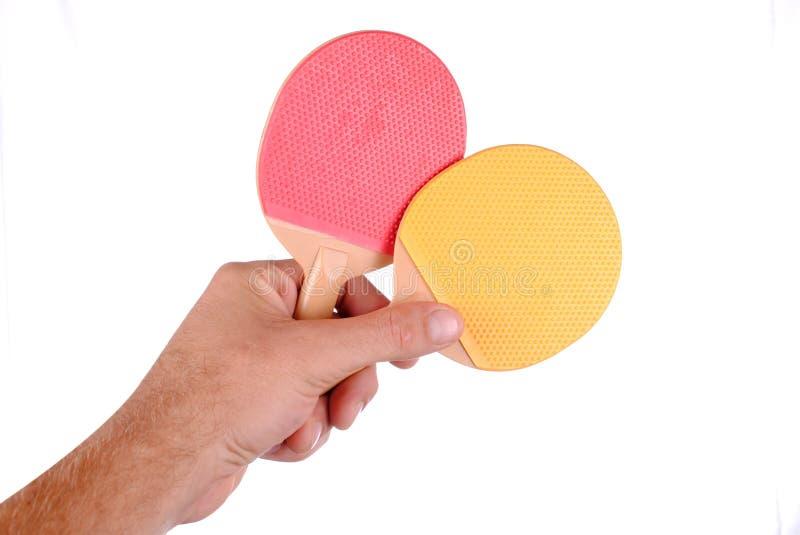 La main retient deux raquettes de ping-pong photographie stock