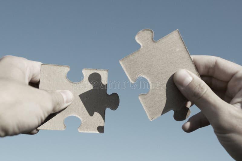 La main retient le puzzle sur un fond du ciel photo libre de droits
