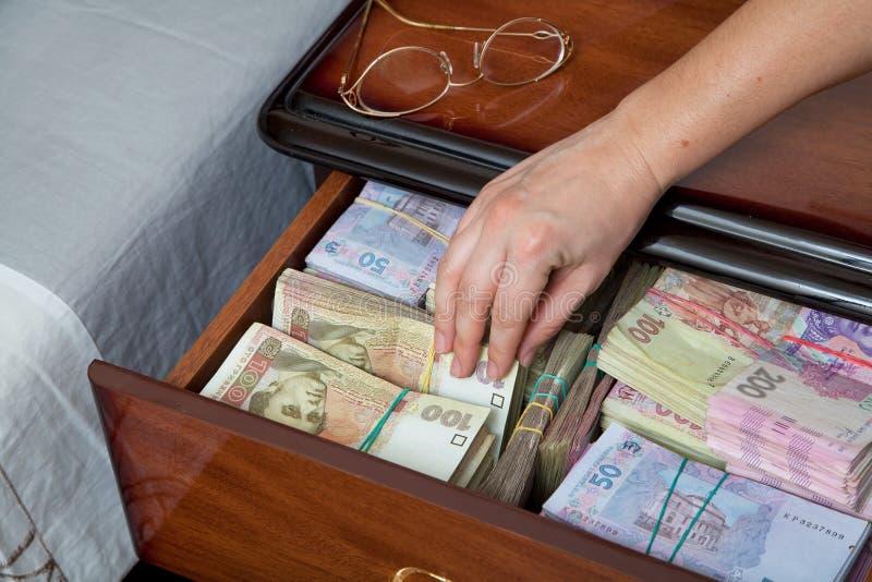 La main retire le billet de banque de la table de chevet photographie stock