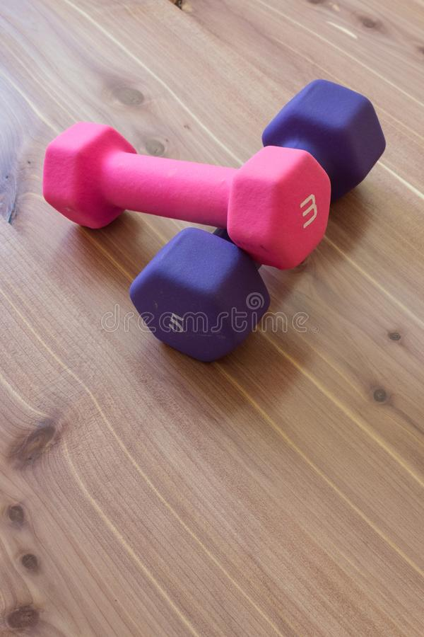 La main rose et pourpre pèse des barbells sur le fond en bois de grain, l'espace de copie image stock