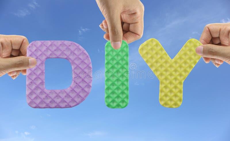 La main s'chargent de l'alphabet DIY de l'acronyme le font vous-même dans créatif image libre de droits