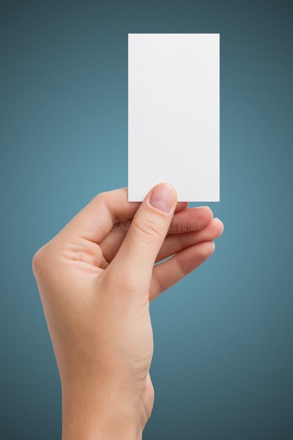 La main tenant la carte vierge blanche de visite d'affaires, cadeau, billet, passage, présentent d'isolement sur le fond bleu Cop photos libres de droits
