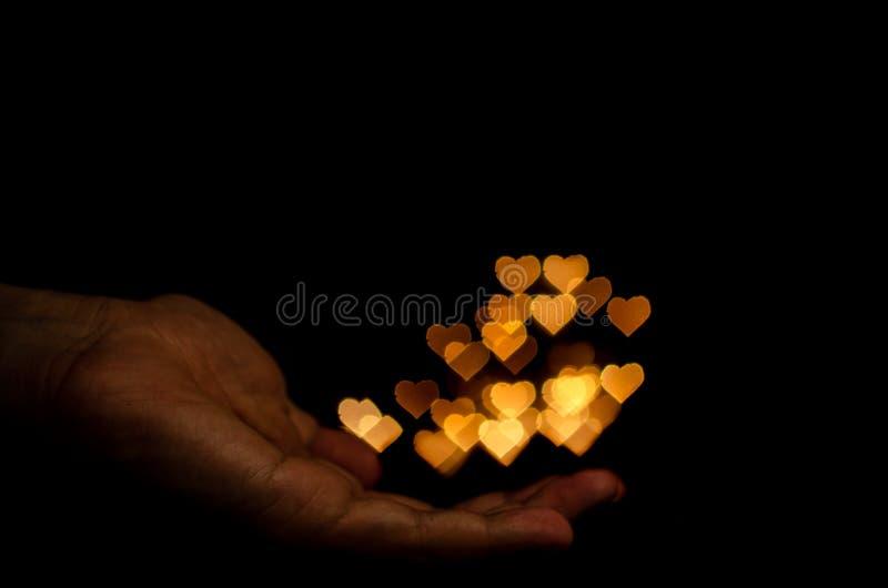 La main tenant la lumière jaune de bokeh de forme d'amour pour la Saint-Valentin images libres de droits