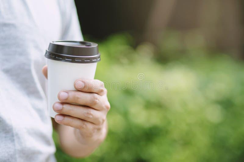 La main tenant la tasse de papier de emportent le café potable sur la lumière du soleil naturelle de matin extérieure endroit de  photographie stock