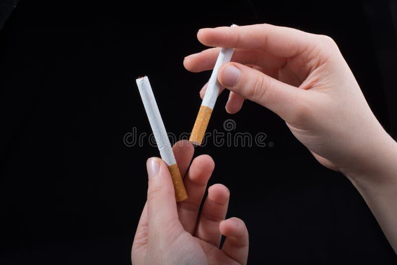 La main tient des cigarettes sur le fond noir image libre de droits