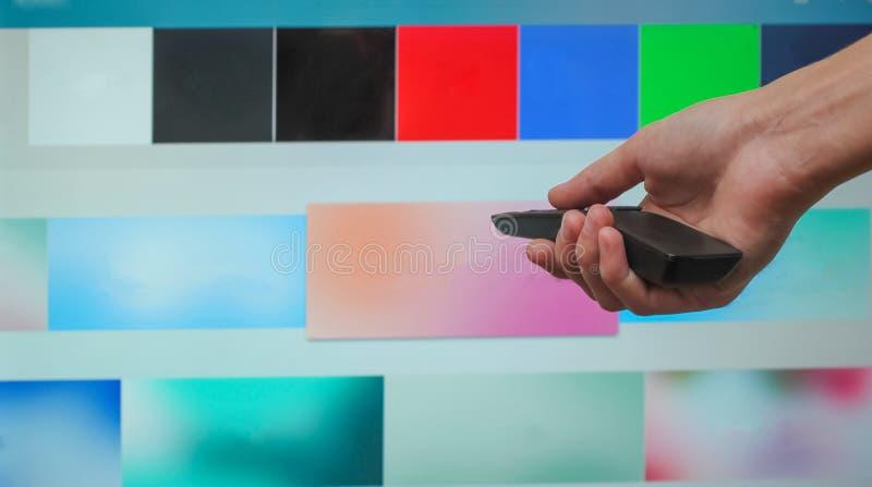 La main tient l'extérieur de TV sur le fond de l'écran intelligent de TV photos stock