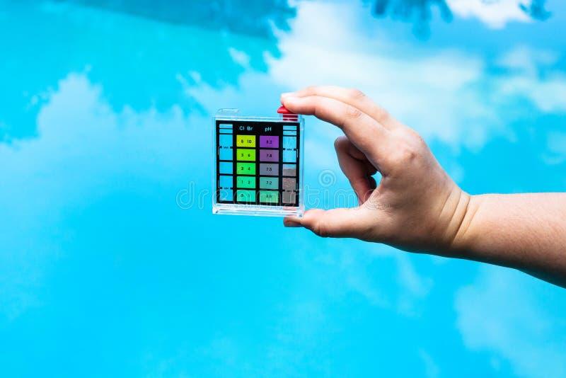 La main tient l'indicateur de pH de la mesure l'acidité photos libres de droits