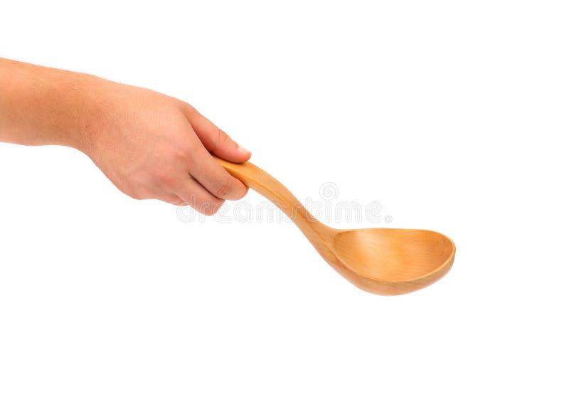 La main tient la cuillère en bois. images stock
