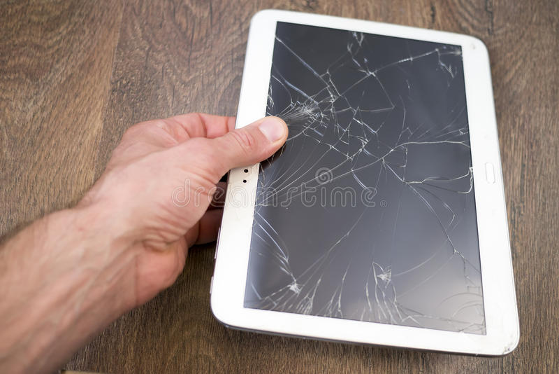 La main tient la tablette avec l'écran tactile cassé images stock