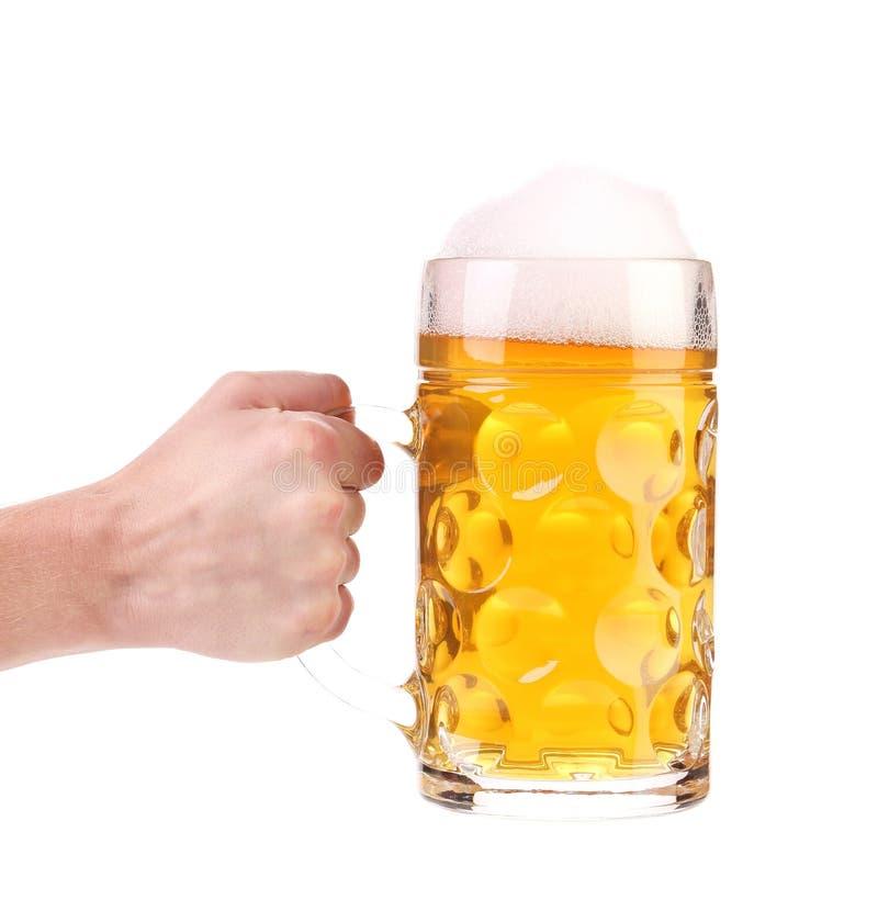 La main tient la tasse de bière avec la mousse. photos libres de droits