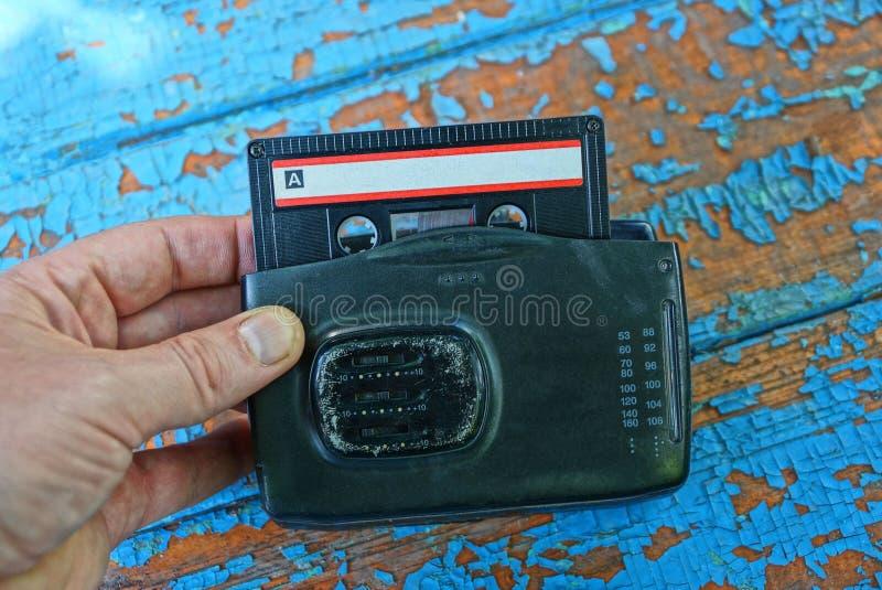 La main tient le vieux joueur audio noir avec la cassette images libres de droits