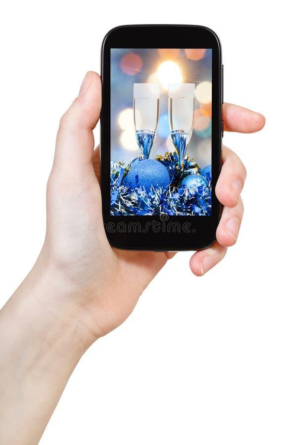 La main tient toujours le téléphone mobile avec la vie de Noël image stock