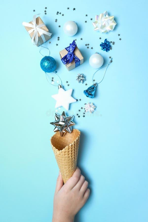 La main tient un cône de gaufre avec des éléments de noël sur fond bleu Concept de vacances images stock