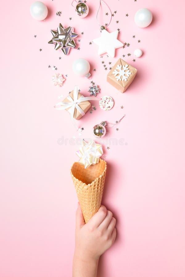 La main tient un cône de gaufre avec des éléments de noël sur fond rose Concept de vacances photographie stock