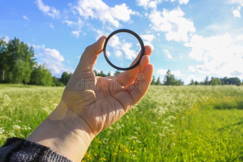 La main tient un filtre circulaire de polariseur sur le fond de champ photographie stock libre de droits