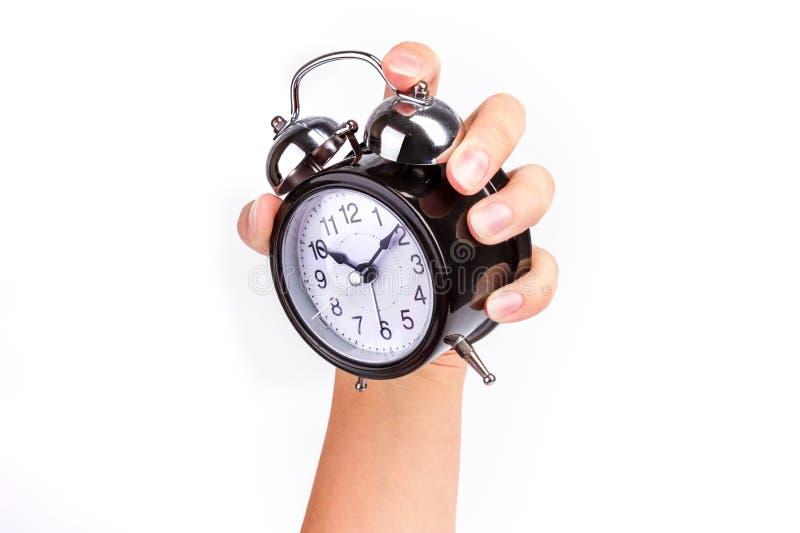 La main tient un réveil brillant noir sur le fond blanc photographie stock