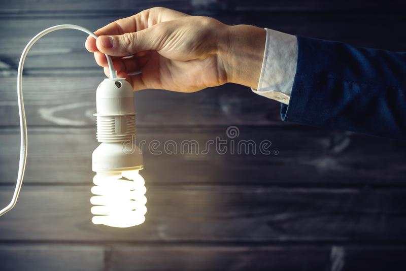 La main tient une ampoule rougeoyante Idée créative dans les affaires photos stock