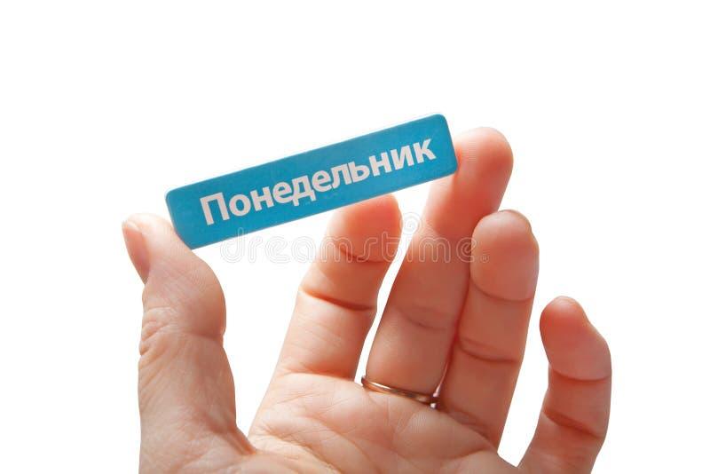 La main tient une carte miniature avec le ` de lundi de ` d'inscription dans le Russe image libre de droits