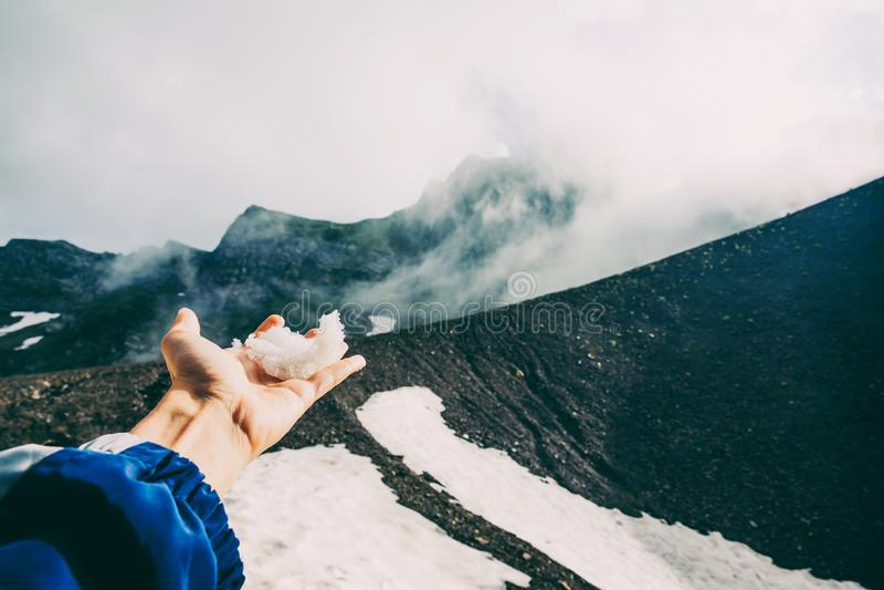 La main touchant la neige par les montagnes de Sotchi de brouillard de nuages aménagent l'été en parc émotif d'aventure de concep photos libres de droits