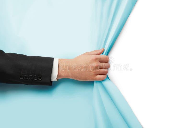 La main tourne le papier bleu image stock