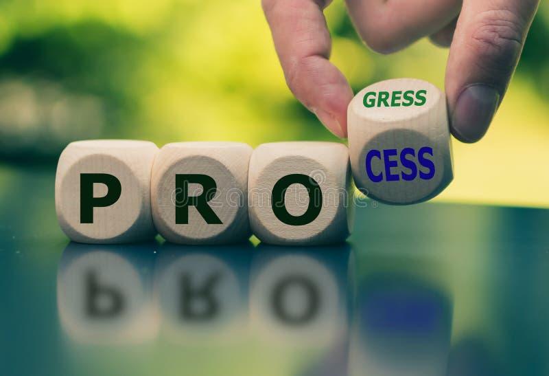 """La main tourne un cube et """"progrès """"de processus """"change mot image libre de droits"""