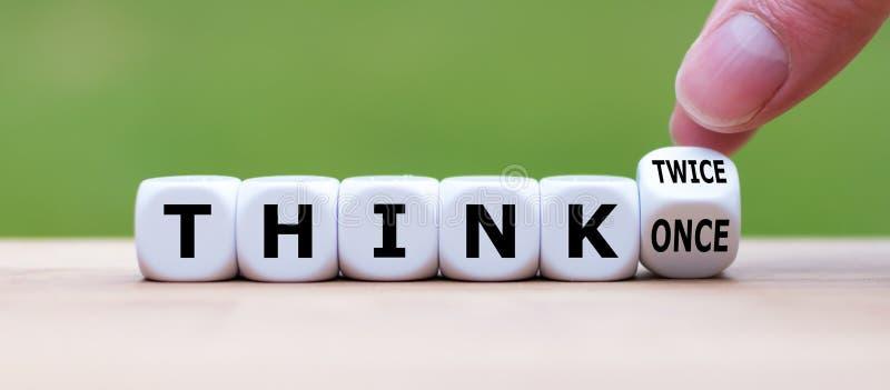 """La main tourne une matrice et change l'expression """"pensent les once """"pour penser deux fois """" photo stock"""