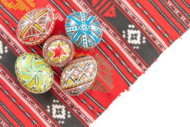 La main traditionnelle roumaine a décoré des oeufs de pâques sur une nappe traditionnelle avec l'espace blanc de copie photographie stock