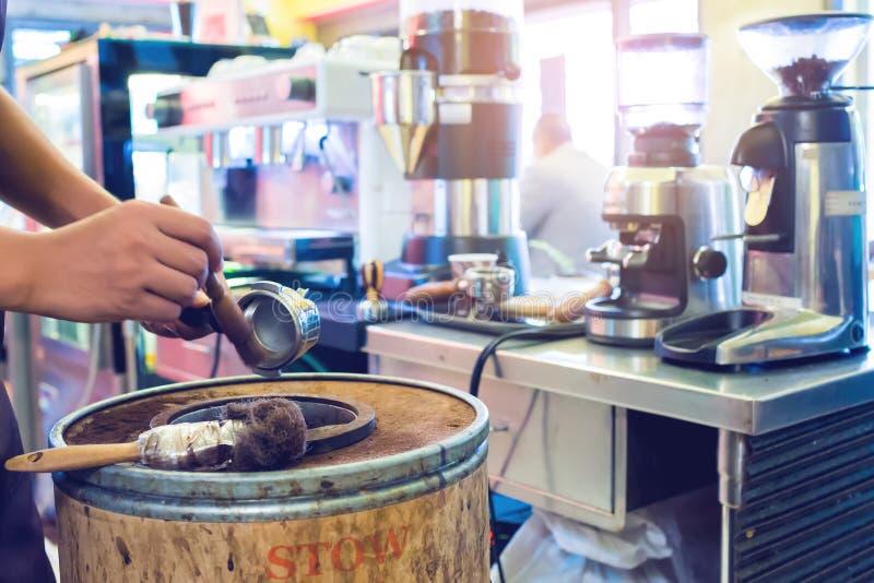 La main trouble versent le caf? moulu de la machine dans un seau en bois avec la machine trouble de caf? au compteur de barre dan images libres de droits