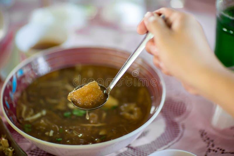 La main utilise une cuillère pour écoper la soupe à style chinois ; ou gueule braisée de poissons en sauce au jus rouge avec les  photo libre de droits