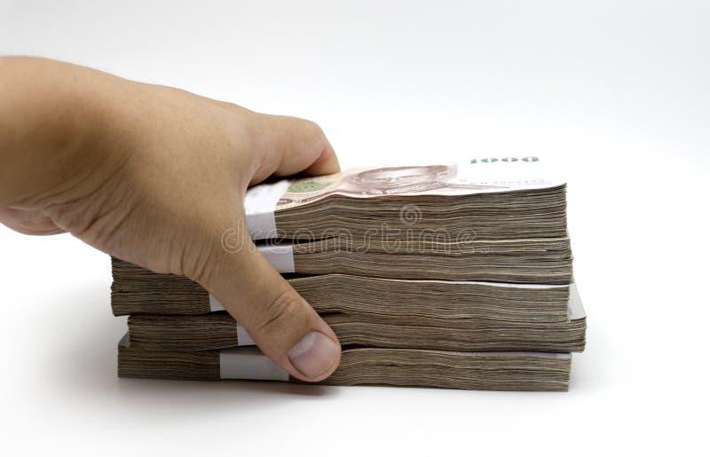 La main volent la note d'argent de baht thaïlandais sur le blanc images stock