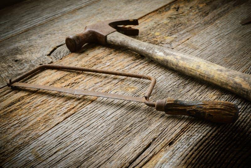 La main a vu et marteau sur le bois rustique photo libre de droits