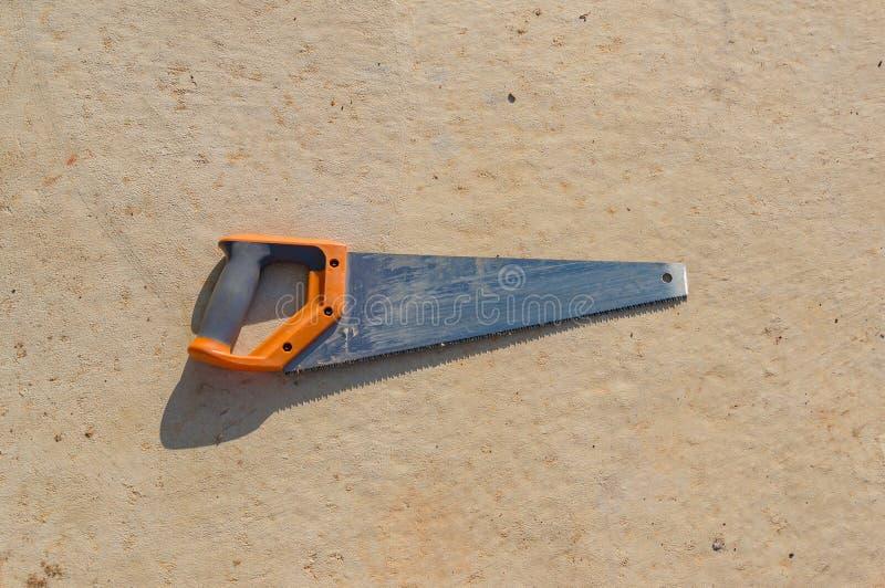 La main a vu sur le fond concret de texture Stil d'outils de construction photos stock
