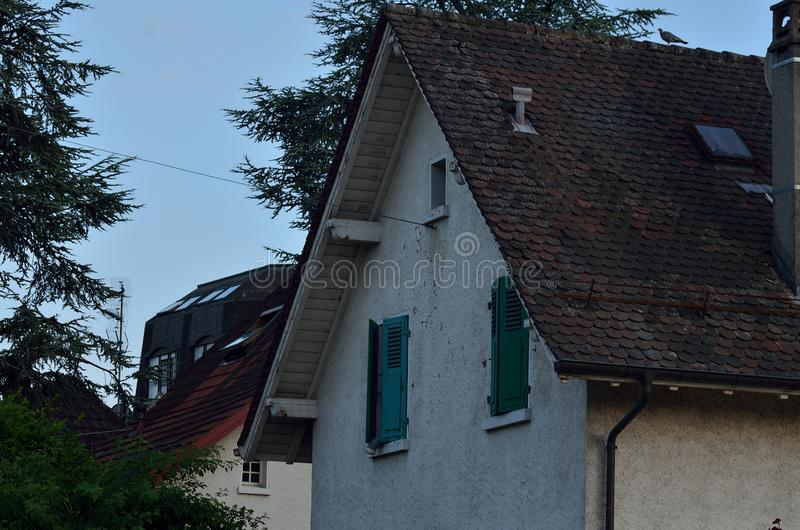 La maison avec les fenêtres vertes photo stock