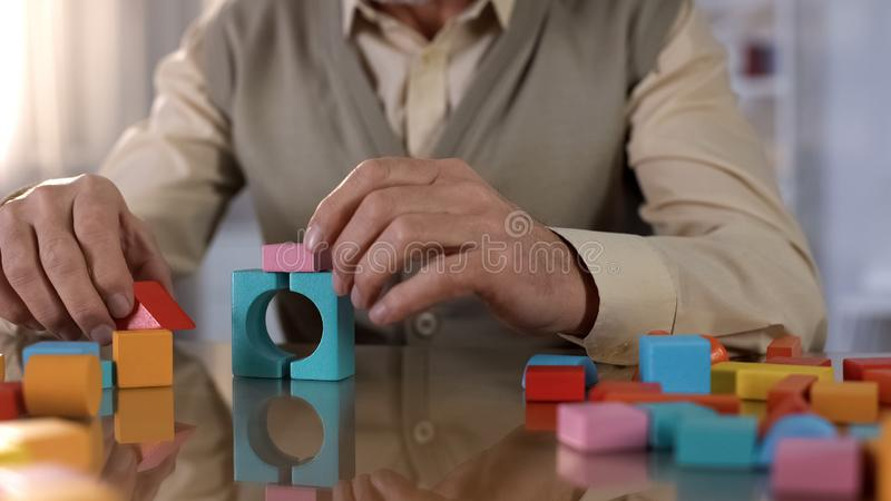 La maison de fabrication masculine pluse âgé a coloré les cubes en bois, exercice de concentration, thérapie photos libres de droits