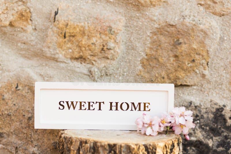 La maison douce se connectent un tronc en bois Fond de mur en pierre image stock
