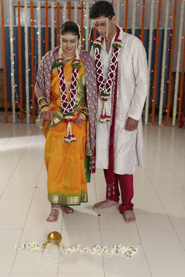 La maison du marié entrant de jeune mariée indoue indienne après l'avoir épousé en poussant le pot a rempli du riz avec son pied. photos libres de droits