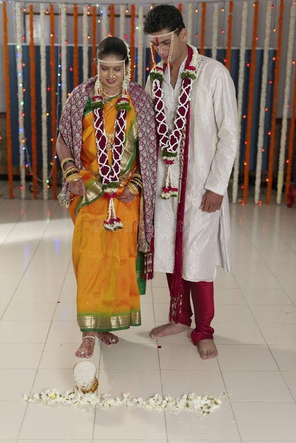 La maison du marié entrant de jeune mariée indoue indienne après l'avoir épousé en poussant le pot a rempli du riz avec son pied. images libres de droits
