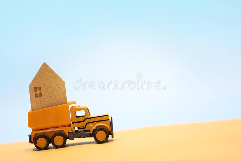 La maison en bois continuent le camion jaune de jouet dans le d?sert sous le ciel bleu photos libres de droits