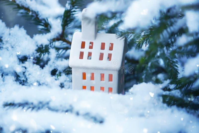 La maison en céramique de lanterne avec la bougie brûlante sur la neige a couvert des branches de sapin en parc d'hiver images stock
