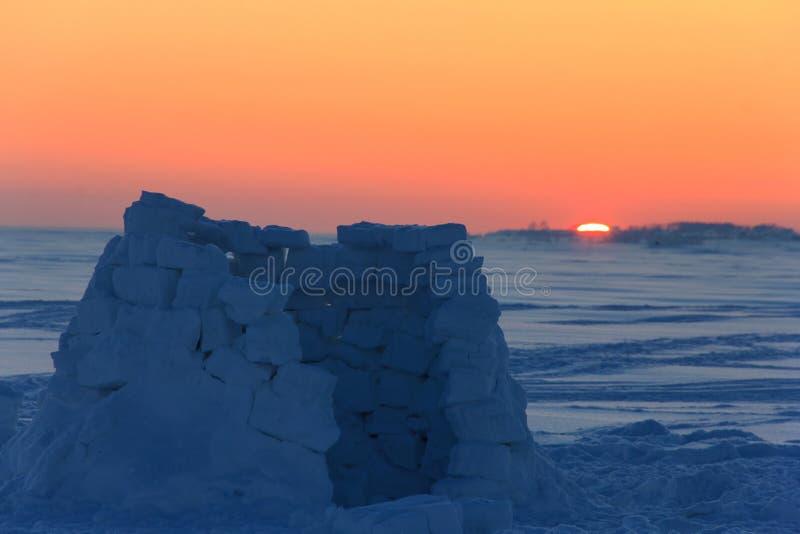 La maison neigeuse d'igloo est non finie et est vide au coucher du soleil au milieu d'un champ couvert de neige abandonné image libre de droits