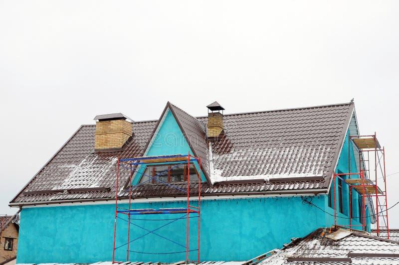 La maison répare dehors Gouttière sur le dessus de toit de la maison Toit en métal Gardes de neige de toit Tuyau de cheminée images libres de droits