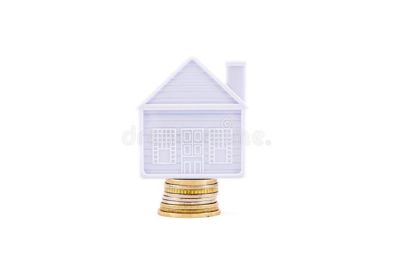 La maison se tient sur quelques pièces de monnaie d'isolement photos stock