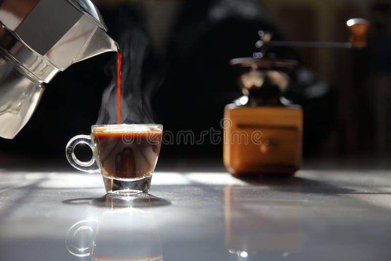 La maison traditionnelle préparent le café d'expresso se renversant dans une petite tasse avec la broyeur sur le fond foncé par l image stock