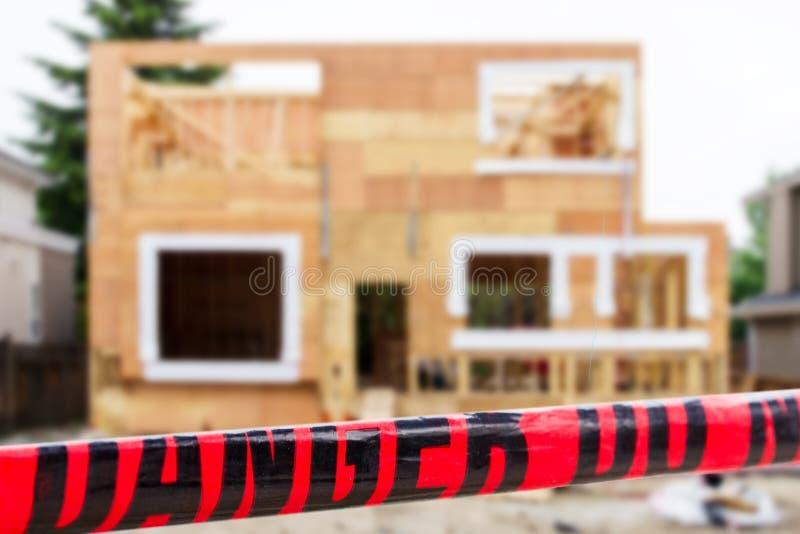 La maison unifamiliale en construction avec le danger d'avertissement rouge de lecture de ruban ne croisent pas images libres de droits