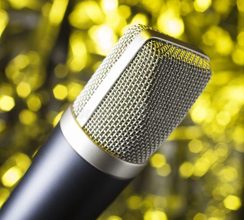 La malla cubrió el micrófono en un fondo amarillo imagenes de archivo
